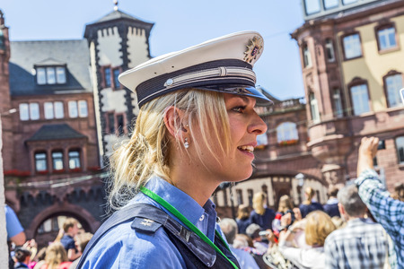 queen elizabeth: FRANKFURT, GERMANY - JUNE 26, 2015: friendly police woman pays attention for the visit of queen Elizabeth II at the Roemer market square in Frankfurt, Germany.