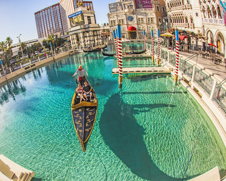 flutter: lAS VEGAS - JUNE 15, 2012: people enjoy the gondola at Venetian Resort Hotel & Casino. The resort opened on May 3, 1999 with flutter of white doves, sounding trumpets, singing gondoliers and actress Sophia Loren.