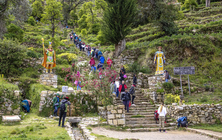 islas: YUMANI, BOLIVIA - JAN 20, 2015: tourists climb up the old incan steps to the temple in Yumani, Bolivia. People live at this islas del sol in the Titicaca lake and earn money by tourism. Editorial