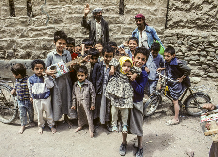 selfmade: SHIBAM, YEMEN - JAN 1, 1991: family with other children pose for photo in Shibam, Yemen. They carry hand made toys with them like selfmade guitar. Editorial