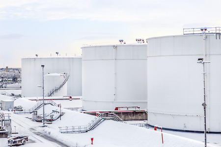 l petrol: white tanks in tank farm with iron staircase in snow Stock Photo
