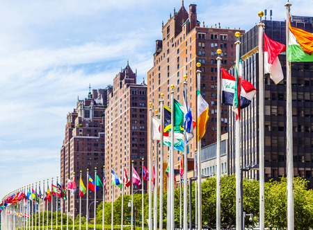 un: NEW YORK, USA - JULY 12, 2015: United Nations Headquarters with flags of the members of the UN in New York.  The complex has served as the official headquarters of the UN since  1952.