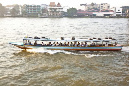 fareast: BANGKOK, THAILAND - DEC 23, 2009: people in the boat at the river Mae Nam Chao Phraya in Bangkok, Thailand. More than 15 boat lines operate on the river including commuter lines.