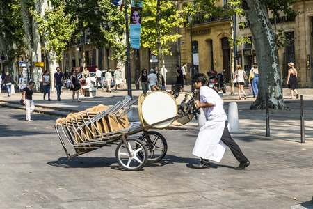the place is outdoor: AIX EN PROVENCE, FRANCE - JULY 8, 2015: waiter carries tables for the outdoor restaurant with a sack barrow to the place. in Aix many restaurants serve outdoor dinner.