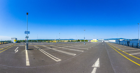 a lot  of: empty outdoors parking area under blue sky