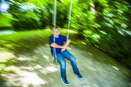 freising: cute boy has fun going on the swings