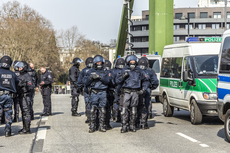 demonstrate: FRANKFURT, GERMANY - MAR 18, 2015: police pays attention for people demonstrate against EZB and Capitalism in Frankfurt, Germany. 9 tsd policemen guard the demo.