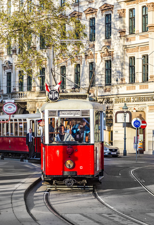 electric tram: VIENNA, AUSTRIA - APR 25 2015: Old red tram waiting for people on the stop.  On January 28, 1897, an electric tram operated for the first time in Vienna on the tracks of todays line 5.