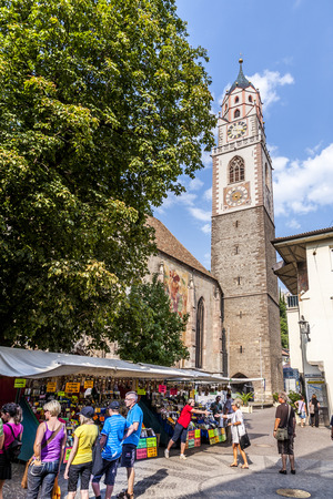 meran: MERAN, ITALY - AUG 1, 2015: typical market in front of St. Nicholas Church in Meran, Italy. The church is dedicated to Saint Nicholas, the patron saint of the town.