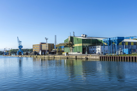famous industries: WOLGAST, GERMANY - AUG 13, 2015: view at river Peene to dockyard area in Wolgast. The Peene dockyard was founded in 1948 by the russian troups. Editorial