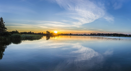 backwater: sunset in Zinnowitz under clear sky with reflection in the backwater Stock Photo