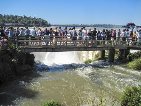 admire: IGUACU, BRAZIL - JULY 30, 2015: Tourists admire Iguacu (Iguazu) falls on a border of Brazil and Argentina Editorial