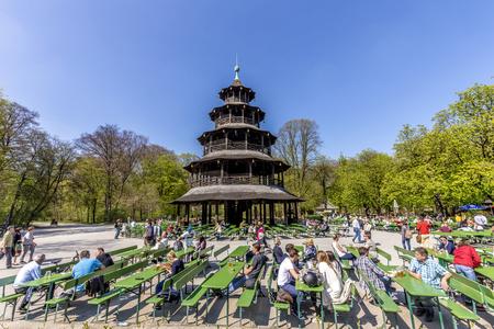 MUNICH, GERMANY - APR 20, 2015: people enjoy the  Biergarten near Chinese tower in English garden in Munich, Bayern, Germany.