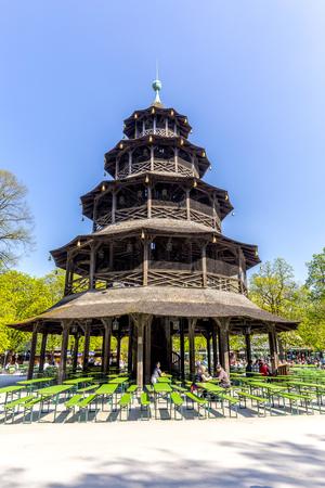 biergarten: MUNICH, GERMANY - APR 20, 2015: people enjoy the  Biergarten near Chinese tower in English garden in Munich, Bayern, Germany.