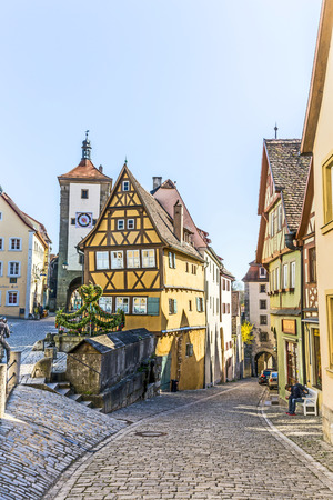 der: ROTHENBURG, GERMANY - APR 19, 2015: people at the market place of Rothenburg ob der Tauber, Germany. The medieval town attracts over 2 million visitors every year.