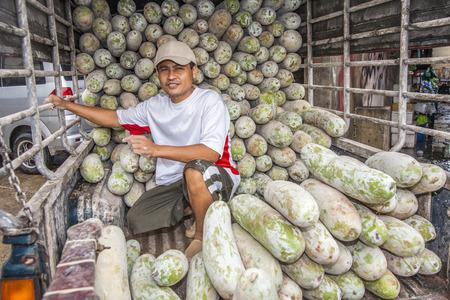 BANGKOK, THAILAND - 12 mei: ongeïdentificeerde man transporteert grote kokospalmen in zijn auto in Bangkok, Thailand. De avondmarkt sluit in de vroege ochtend en mensen rijden terug.