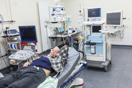 emergency case: USINGEN, GERMANY - MAR 15, 2015: Sick senior man  lying in an emergency room in a new  hospital in Usingen, Germany. In Germany every person in emergency case must be reached latest within 17 minutes. Editorial