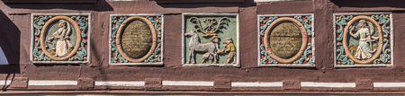 half timbered house: traditional carving at an half timbered house with colored symbols Stock Photo