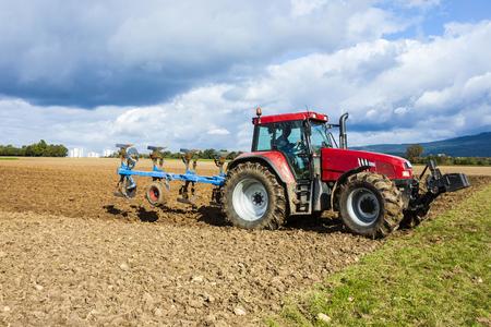 arando: tractor arando un campo bajo las nubes oscuras