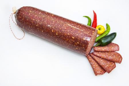 Salame con peperoni isolato su bianco