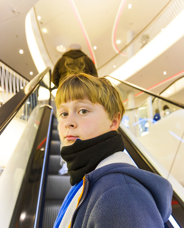 self confident: child on moving staircase looks self confident and smiles Stock Photo