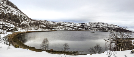 snow covered mountains: scenic lake  in Norway and snow covered mountains with clouds