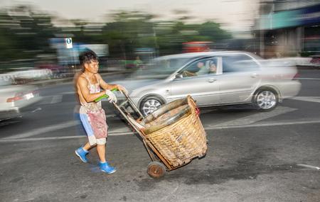 BANGKOK, THAILAND - 23 december 2009: man rijdt naar huis met zijn barrow van nacht markt Pak Khlong Thalat in Bangkok, Thailand. De markt is de oudste bloemenmarkt in Thailand.