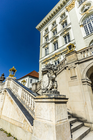 nymphenburg palace: MUNICH, GERMANY- APR 20, 2015: facade of Nymphenburg castle with bavarian lion and crest in Munich, Germany. The garden is free for public.