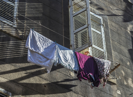 immigrants: MARSEILLE, FRANCE, JULY 9, 2015: woman with scarf pegs out the washing on a washing line in front of the facade in marseilles, France. Marseille has a high percentage of immigrants due to harbor.