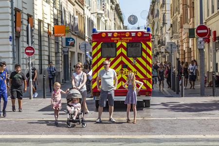 reanimation: MARSEILLE, FRANCE, JULY 10, 2015: family waits at the sideway to cross the street. An ambulance car with reanimation parks in the pedestrian street.