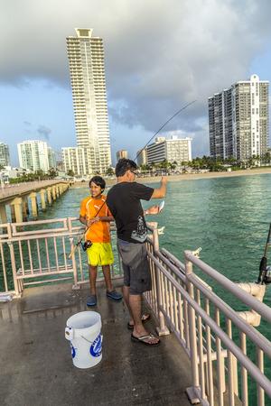 magnate: SUNNY ISLES BEACH, USA - AUG 17, 2014: people catch fishes at  the pier in Sunny Isles Beach, USA. In 1936, Milwaukee malt magnate Kurtis built the Sunny Isles pier. Editorial