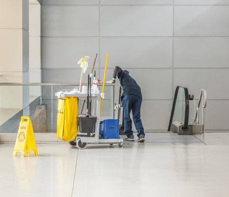 charlady: LOS ANGELES, USA - AUG 31, 2014: cleaning lady with her cleaning trolley cleans the glass of a staircase in Los Angeles international airport. Cleaners are organized in a trade union.
