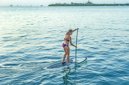 standing up: KEY WEST,  USA - AUG 26, 2014: woman enjoys Stand Up Paddle Surfing in Key West. Coastal cultures have stood up within canoes and paddled standing for thousands of years.