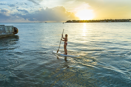stood up: KEY WEST,  USA - AUG 26, 2014: woman enjoys Stand Up Paddle Surfing in Key West. Coastal cultures have stood up within canoes and paddled standing for thousands of years.