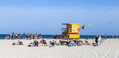 lifeguard tower: MIAMI, USA - AUGUST 18, 2014 : People do fitness training at the beach next to a lifeguard tower. South beach is famous for its white sand.