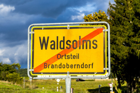 describes: WALDSOLMS, GERMANY - SEP 19, 2015: Street sign Waldsolms, village of Brandoberndorf in Waldsolms. The red stripe describes that you leave the village.