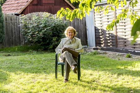 chair garden: elderly woman sits in the plastic chair in her garden and enjoys the sun