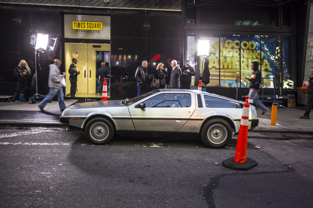 25th: NEW YORK, USA - AUG 21, 2015:  people admire the famous original amc chrome car from the film back to the future presented at time square due to 25th anniversary of the Hollywood film.