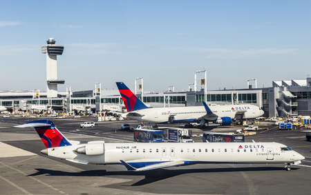 NEW YORK, USA - OCT 20, 2015: Air Traffic Control Tower and Terminal 4 with Delta Air planes at the gates in JFK Airport in NY. 1963 the airport was rededicated John F. Kennedy International Airport. Editorial
