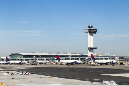 NEW YORK, USA - OCT 20, 2015: Air Traffic Control Tower and Terminal 4 with Delta Air planes at the gates in JFK Airport in NY. 1963 the airport was rededicated John F. Kennedy International Airport. 報道画像