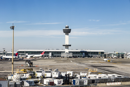 jfk: NEW YORK, USA - OCT 20, 2015: Air Traffic Control Tower and Terminal 4 with Air planes at the gates in JFK Airport in NY. 1963 the airport was rededicated John F. Kennedy International Airport.
