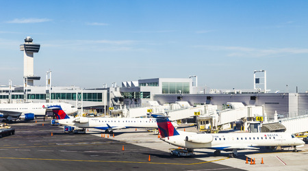 Kennedy: NEW YORK, USA - OCT 20, 2015: Air Traffic Control Tower and Terminal 4 with Delta Air planes at the gates in JFK Airport in NY. 1963 the airport was rededicated John F. Kennedy International Airport. Editorial