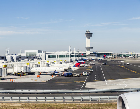 jfk: NEW YORK, USA - OCT 20, 2015: Air Traffic Control Tower and Terminal 4 with Delta Air planes at the gates in JFK Airport in NY. 1963 the airport was rededicated John F. Kennedy International Airport. Editorial