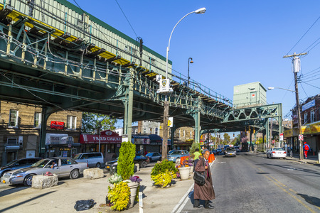 lots people: NEW YORK, USA - OCT 20, 2015: people at the crossing at Metro station New Lots Av Avenue in east New York build as elevated train in New York, USA. The red line connects east with north west New York. Editorial