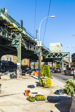 new car lots: NEW YORK, USA - OCT 20, 2015: people at the crossing at Metro station New Lots Av Avenue in east New York build as elevated train in New York, USA. The red line connects east with north west New York. Editorial