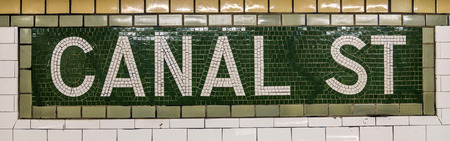 describe: New York, USA - OCT 22, 2015: old vintage sign canal Street Subway Station in Manhattan. Intricate tiles with symbols  in terra cotta describe the place.