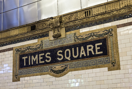 describe: New York, USA - OCT 22, 2015: old vintage sign times square Subway Station in Manhattan. Intricate tiles with symbols  in terra cotta describe the place.