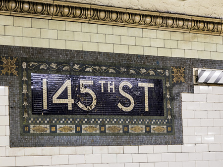 describe: New York, USA - OCT 22, 2015: old vintage sign 145th street Subway Station in New York. Intricate tiles with symbols  in terra cotta describe the place.