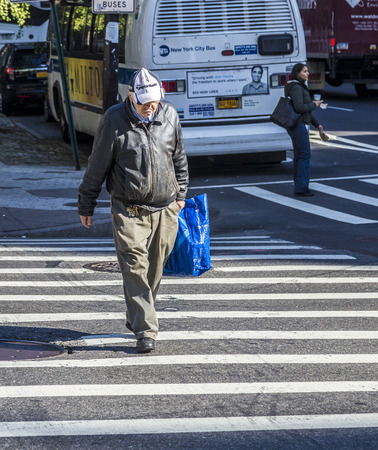 annually: NEW YORK, USA - OCT 21 2015: people crossing a street at a pedestrian crossing in New York. New York State averages nearly 300 pedestrian fatalities annually. Editorial