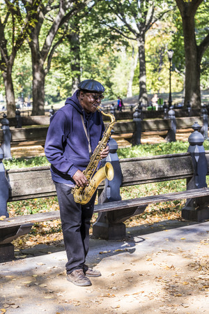 boroughs: NEW YORK, USA - OCT 21, 2015: Performer plays sax at Central Park in New York, USA. One of the 5 boroughs of New York City, the smallest but also the most populated
